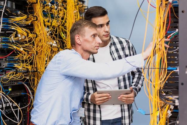 Молодые сетевые инженеры, работающие в серверной комнате