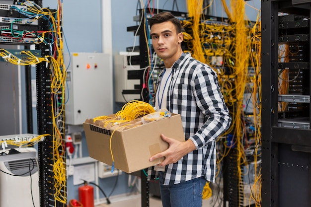Молодой человек держит коробку с проводами среднего снимка