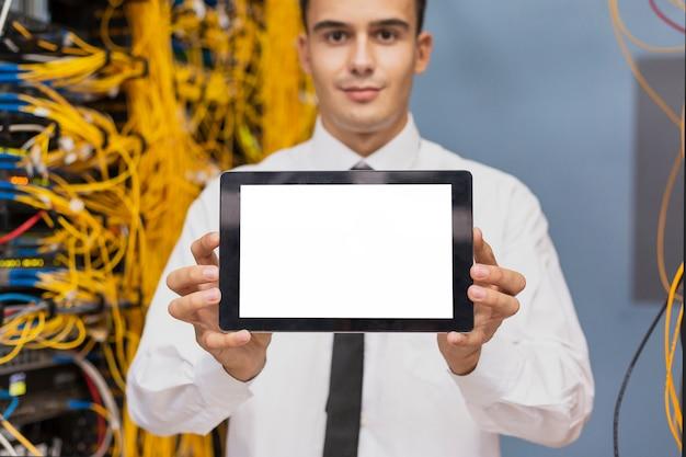 タブレットのモックアップを持つ若いビジネスエンジニア