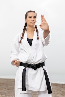 Молодая девушка в одежде каратэ на открытом воздухе