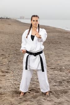 Подходит молодая девушка в костюме каратэ