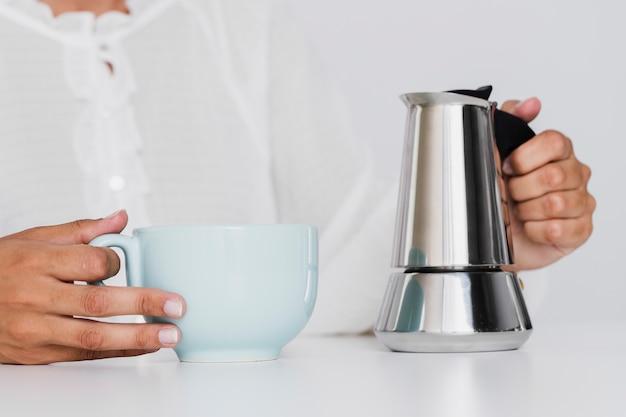 Человек держит керамическую чашку и чайник