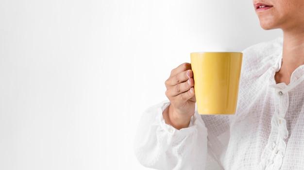 Крупным планом лицо, занимающее желтую чашку