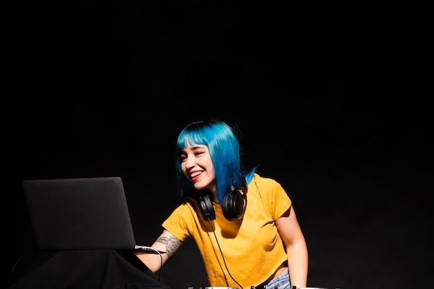 Вид спереди женщина диджей, проверка настроек на ноутбуке