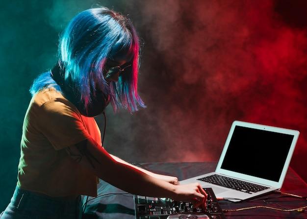Вид сбоку женщина-диджей в клубном микшировании