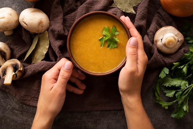 Крупным планом лицо, занимающее миску с тыквенным супом