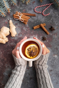 熱いお茶とマグカップを保持しているクローズアップの女性