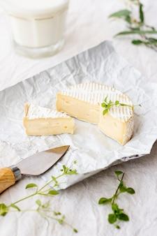 Крупным планом сыр бри и стакан молока