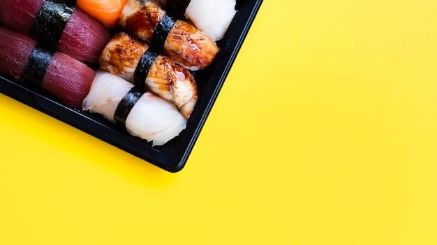 Большая суши черная тарелка на желтом фоне