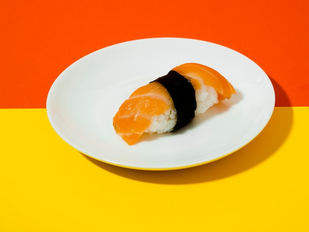 黄色とオレンジ色の背景に白い皿にサーモン寿司