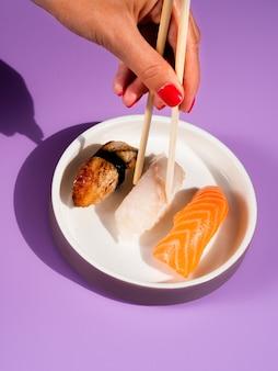 白い皿から箸寿司で取っている女性