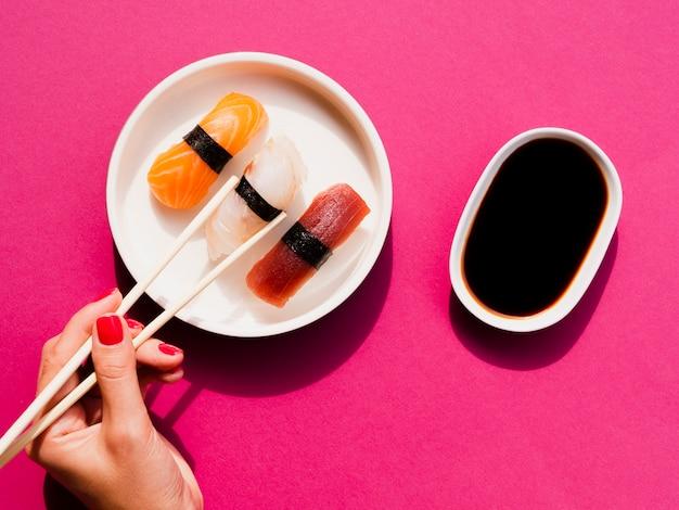 Женщина выбирает суши из тарелки с палочками