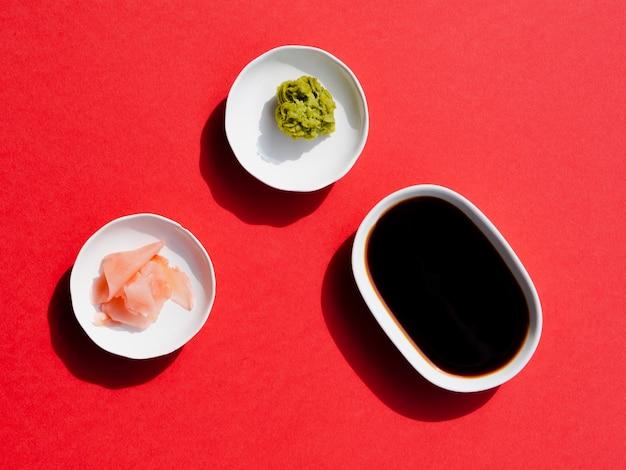 Тарелки с васаби и соевым соусом на красном фоне