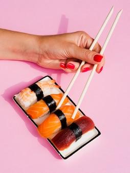 Женщина выбирает лосось суши из тарелки