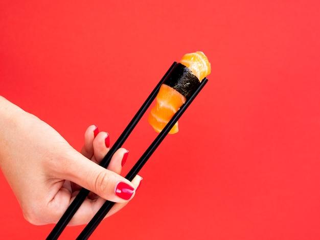 チョップで保持している女性は、赤い背景にサーモン寿司をスティックします。