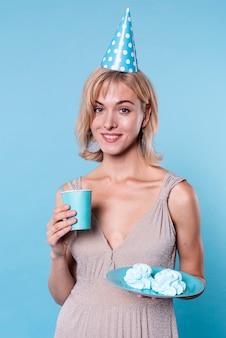 Вид спереди смайлик на день рождения женщина держит тарелку с тортом
