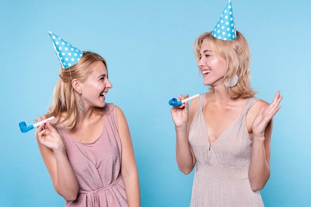 Улыбающиеся подруги на вечеринке по случаю дня рождения