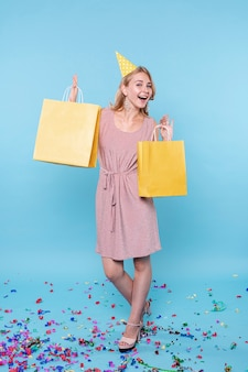 Возбужденный день рождения женщина, держащая подарки сумки