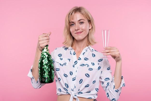 Вид спереди молодая женщина, держащая шампанское на вечеринке