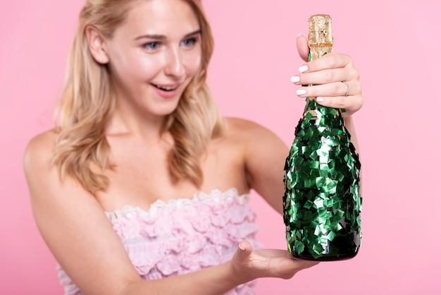 Женщина вид спереди на вечеринке, держа бутылку шампанского