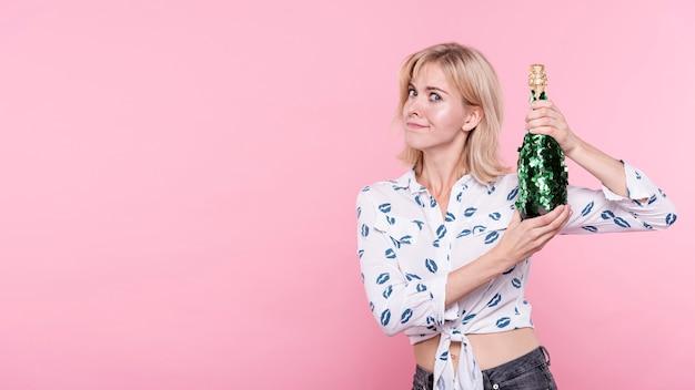 シャンパンのボトルを持つコピースペース若い女性