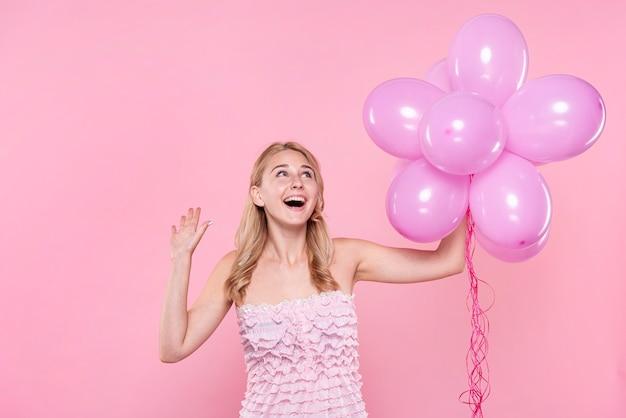 風船を保持しているパーティーで美しい女性