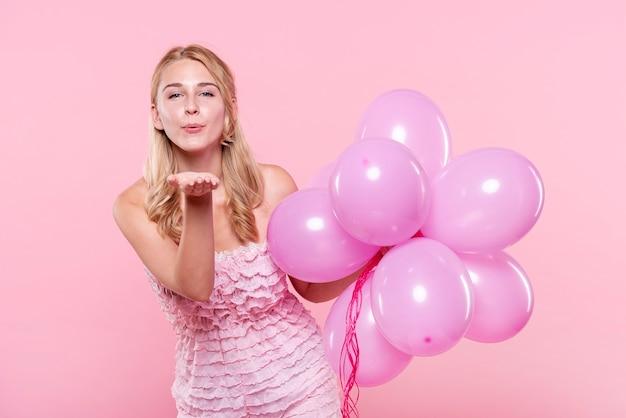 Женщина с воздушными шарами дует поцелуи
