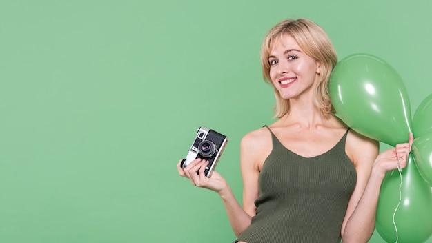 緑の背景にポーズをとってカジュアルな服装の女性