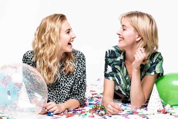 Молодые дамы улыбаются, глядя друг на друга