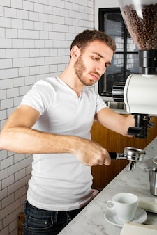 Молодой бариста делает чашку кофе