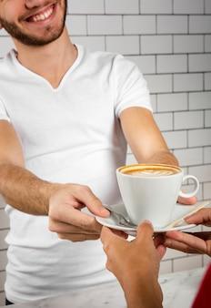 Молодой человек, предлагая чашку капучино