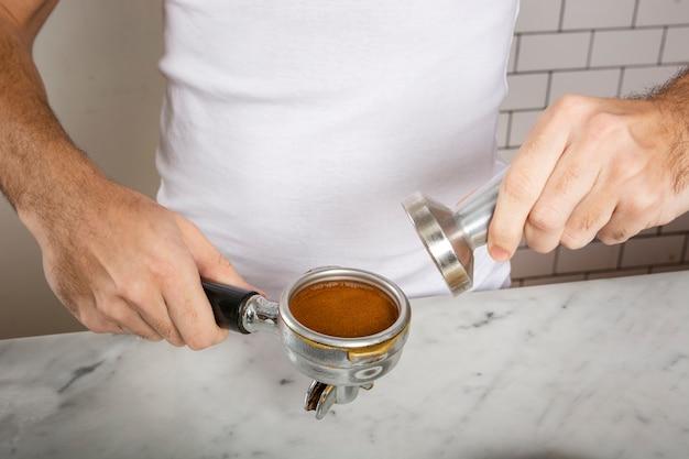 Бариста использует тампер для приготовления кофе