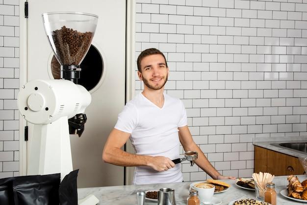 Бариста держит в руке совок для эспрессо с кофейной пудрой