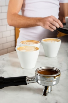 Портафильтр с молотым кофе и тремя чашками кофе