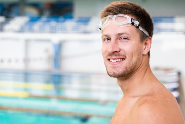 Улыбающийся пловец в бассейне