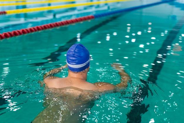 プールで泳ぐ背面図男性