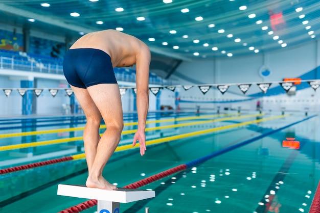 スイミングプールでジャンプする準備をして運動の男