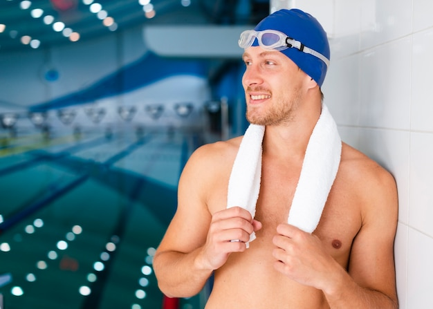 Пловец держит полотенце и смотрит в сторону