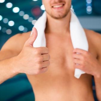 Руки держа полотенце и показывая знак ок