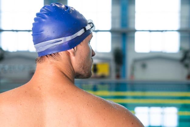 Вид сзади пловец мужского пола, глядя на бассейн