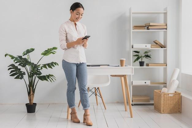 Вид спереди молодая женщина в офисе с помощью мобильного телефона