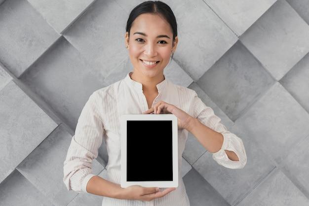 タブレットのモックアップを提示するスマイリーの女性