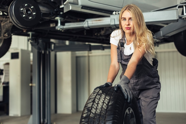 Вид спереди молодой женский механик, толкая колесо