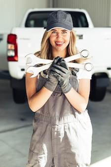Вид спереди молодой и улыбающейся женщины-механика