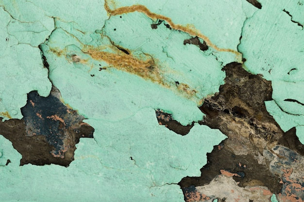 建物の壁からひびが入って剥がれた塗料