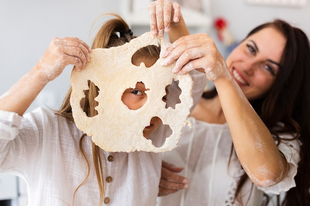Мать и дочь держит тесто для печенья