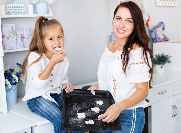 母と娘のクッキーで、トレイを保持します