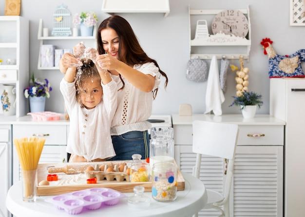 幸せな母と娘が小麦粉で遊んで