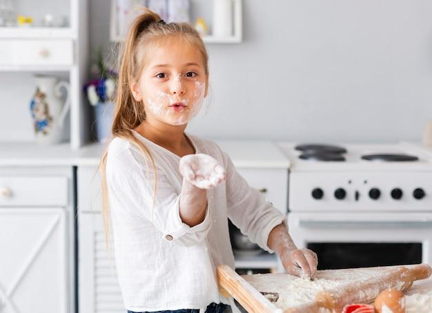 Забавная маленькая девочка, показывая ее руку с мукой