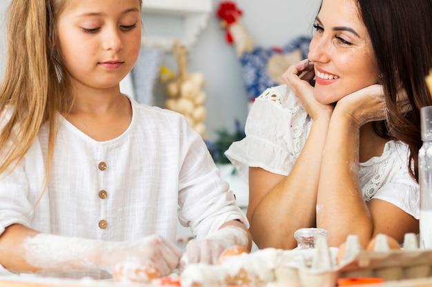 Прекрасная мать и дочь готовит еду